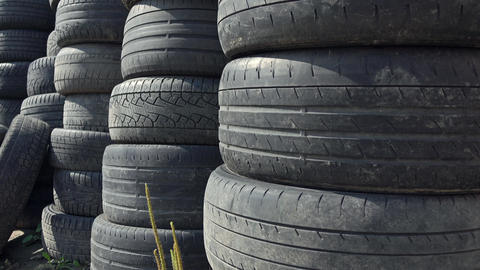 Stacks of old used car tyres 4K zoom in shot. Disposal site Footage