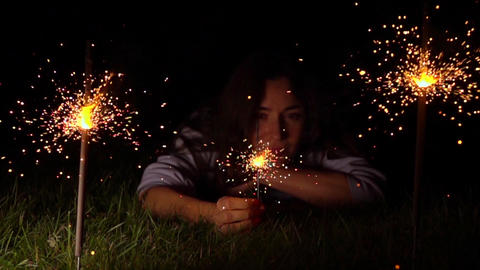 Pensive young woman on the grass with burning sparkler at night. Super slow Footage