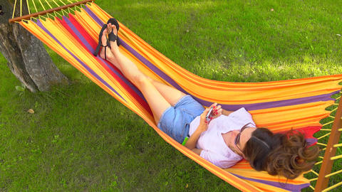 Slender pretty brunette laying in bright hammock and using her mobile phone Footage