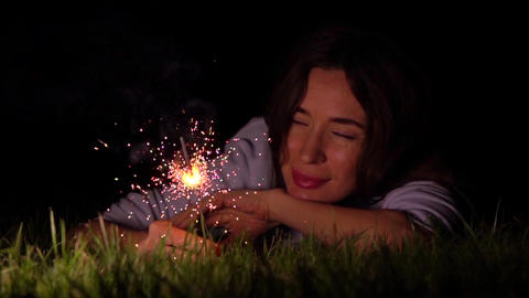 Romantic thoughtful girl laying on the grass with burning sparkler at night Footage