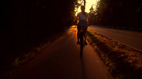 Slim brunette girl riding a bike along summer sunset road. Slow motion tracking Footage