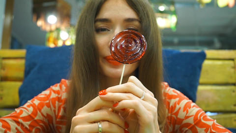 Portrait of beautiful brunette girl turning red sugar candy in her hands Footage