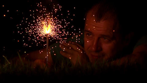 Lonesome mid aged man laying on the grass with burning sparkler at night, close Footage