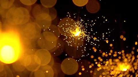 Three orange sparklers against dark background. Super slow motion shallow focus Footage