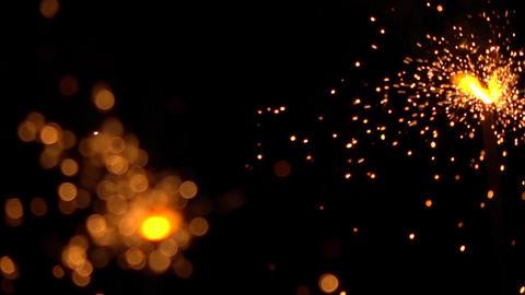 Two orange sparklers against dark background. Super slow motion shallow focus Footage