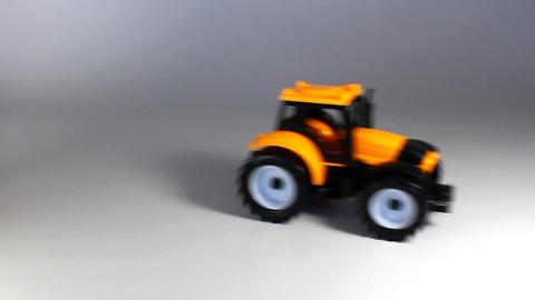 Yellow tractor ride back and stop in white background 영상물