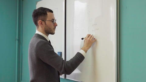 Man teacher writes on white board in class room Footage