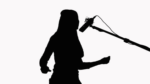 Silhouette of a girl with long hair who sings into a studio microphone. On a Footage