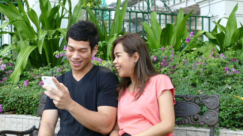 Guy sitting on a bench at Benjasiri Park watching his phone when a girlfriends j Footage