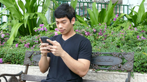 Guy sitting on a bench at Benjasiri Park playing with his iPhone 6S Plus Footage