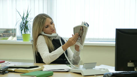 Businesswoman relaxing in the office reading a magazine talking on the phone Live Action