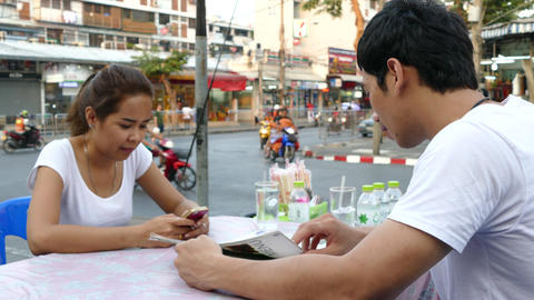 Guy looks at the menu while the girl is looking at her phone Animation
