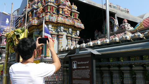 Guy makes a picture with his mobile from the Shri Mariamman Indian Temple Footage