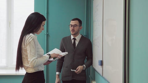 Business man and woman discussing something near whiteboard Live Action