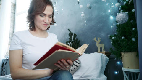 Woman reading a book sitting on a bed Footage