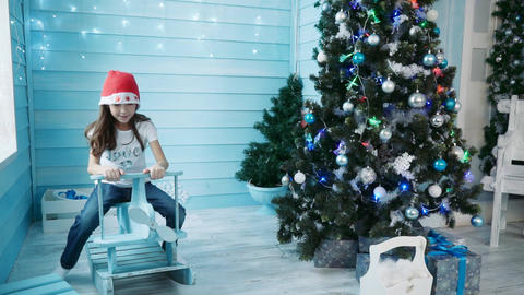 A girl in a red hat sits on a children's rocking chair near the Christmas tree Footage