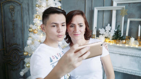 A young man with his beautiful mother on the background of a Christmas tree does Footage