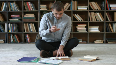 Student with phone taking picture of books page Live Action