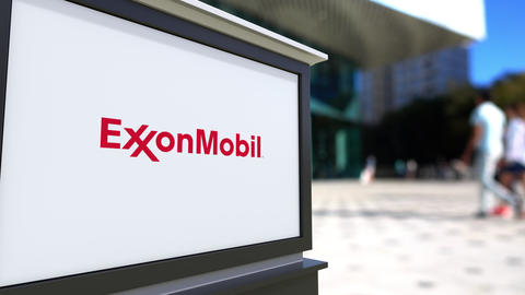 Street signage board with ExxonMobil logo. Blurred office center and walking Footage