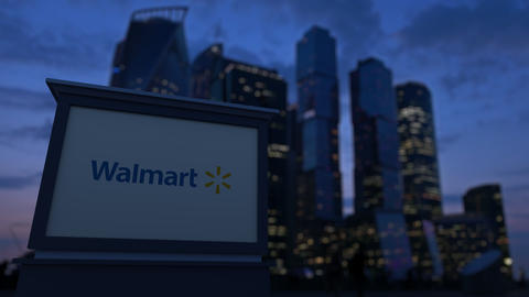 Street signage board with Walmart logo in the evening. Blurred business district Footage