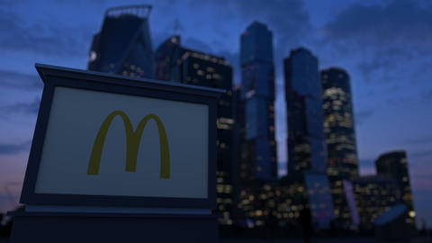 Street signage board with McDonald's logo in the evening. Blurred business Footage