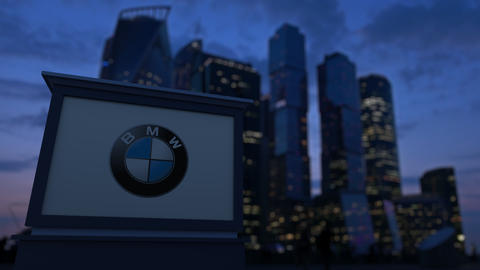 Street signage board with BMW logo in the evening. Blurred business district Live Action
