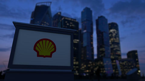 Street signage board with Shell Oil Company logo in the evening. Blurred Footage