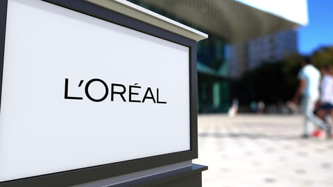 Street signage board with L'Oreal logo. Blurred office center and walking people Footage