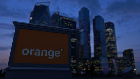 Street signage board with Orange S.A. logo in the evening. Blurred business Footage