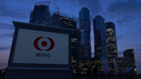 Street signage board with MUFG logo in the evening. Blurred business district Footage