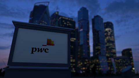 Street signage board with PricewaterhouseCoopers PwC logo in the evening Footage