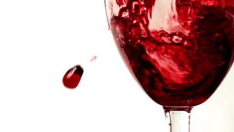 Red wine being poured into wineglass against white background extreme close up Footage