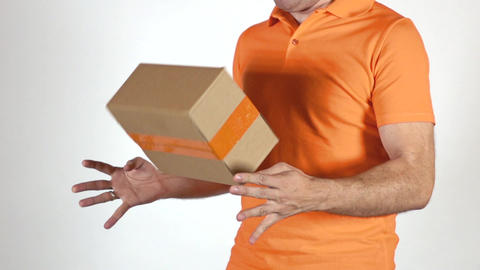 Courier in orange uniform tossing a small parcel. Light gray backround, Super Footage