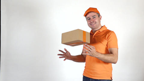 Delivery man in orange uniform tossing a small parcel. Light gray backround Footage