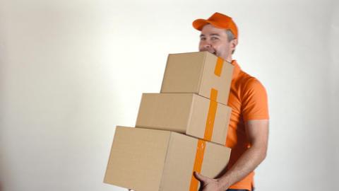 Delivery man in orange uniform delivering big stack of cardboard boxes. Light Footage