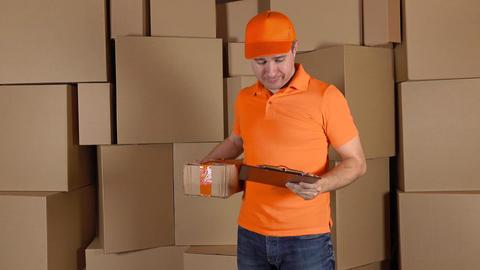 Man in orange uniform delivering heavily damaged parcel to customer. Brown Footage