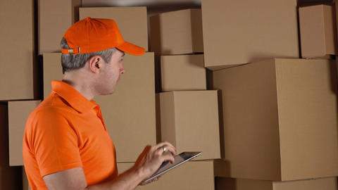Storage worker in orange uniform counting boxes and making records in his tablet Footage