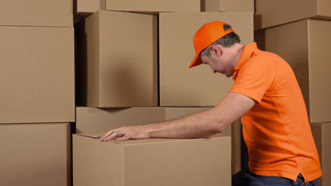Warehouse worker in orange uniform packaging big carton with duct tape gun Footage