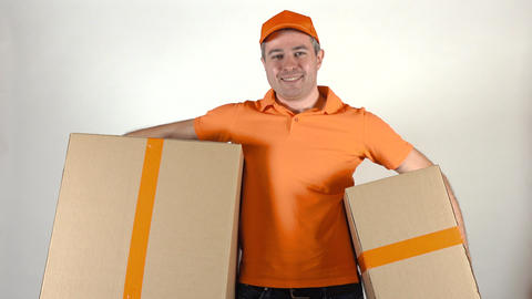 Delivery man in orange uniform delivering two big cartons. Light gray backround Footage