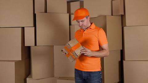 Delivery man in orange uniform delivering damaged parcel to customer. Brown Footage