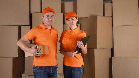 Couriers in orange uniform standing against brown cartboard boxes backround Footage