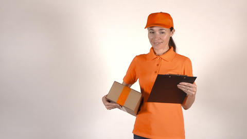 Beautiful female courier in orange uniform delivering a parcel. Light gray Live Action
