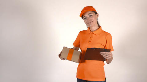 Female courier in orange uniform holding a cardboard box. 4K studio shot Live Action
