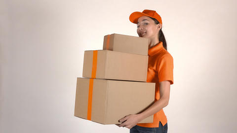 Beautiful girl in orange courier uniform delivering a stack of cartons. Light Live Action