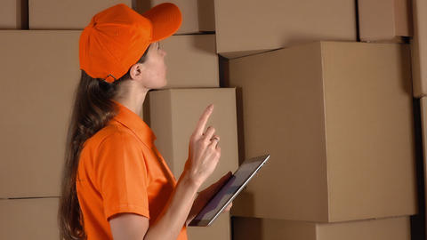 Girl in orange uniform counting storage boxes and using her tablet against brown Footage