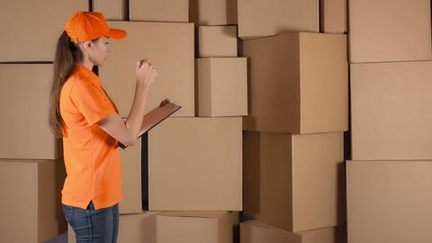 Beautiful female warehouse worker in orange uniform counting items and making Footage