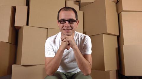 Confident smiling owner of internet shop sitting against multiple carton stacks Footage