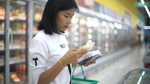 Woman reading food label with ingredients and nutrition facts Footage