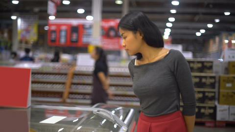 Girl selects semi finished products in freezer at supermarket Footage