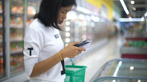 Pretty Thai Woman selects food products in supermarket Footage